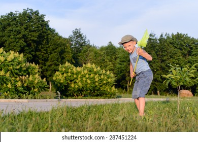 Cute funny little boy wearing hat, sleeveless top and short pants, while running to catch butterflies with a net on the green lawn in a warm day of summer