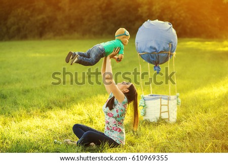 ddd10180 Cute funny little child wearing knitted pilot hat of plays active games  with mommy near handmade