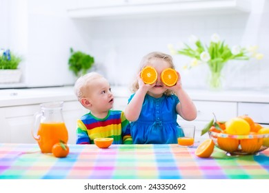 Cute funny little girl and adorable baby boy drinking freshly squeezed orange juice for healthy breakfast in a white kitchen with window on a sunny summer morning