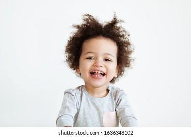 Cute funny little girl against light background