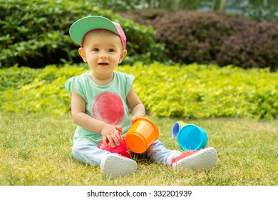 Cute funny little girl baby toddler playing with cups in green garden hat