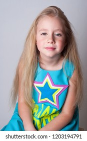 Cute funny little girl dancer with long hair in a blue jumpsuite with a star on a chest sitting on a wooden chair and smiling