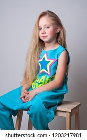Cute funny little girl dancer with long hair sitting on a wooden chair and smiling in a blue jumpsuite with a star on a chest