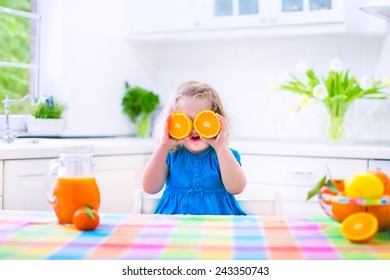 Cute funny little girl drinking freshly squeezed orange juice for healthy breakfast in a white kitchen with window on a sunny summer morning