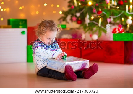 Cute funny little girl sitting under a Christmas tree at home opening her present