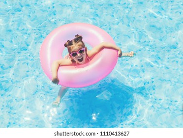 Cute and funny little girl in swimming pool, swimming in Pool Float Ring, wearing sun glasses and having fun. Smmer lifestyle concept