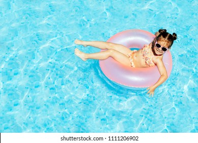 Cute and funny little girl in swimming pool, swimming in Pool Float Ring, wearing sun glasses and having fun. Summer lifestyle concept