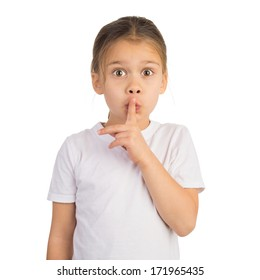 Cute funny little girl trying to attract attention surreptitiously,  holding her index finger against her lips