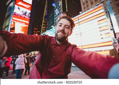 Cute funny man taking selfie on Times Square at night, Manhattan. Inspiring New York atmosphere and a handsome bearded hipster.