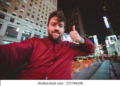 Cute funny man taking selfie on Times Square at night, Manhattan. Inspiring New York atmosphere and a handsome bearded hipster guy.