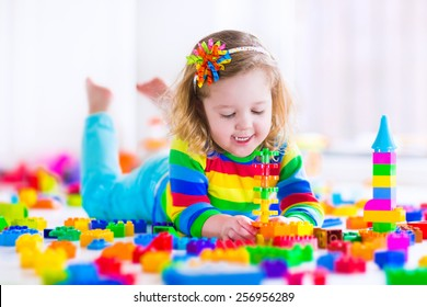 Cute funny preschooler little girl in a colorful shirt playing with construction toy blocks building a tower in a sunny kindergarten room. Kids playing. Children at day care. Child and toys.