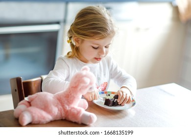 Cute funny toddler girl eating chocolate ice cream at home. Happy healthy baby child feeding plush lama toy with sweet ice-cream. Lovely kid enjoying dessert pudding.
