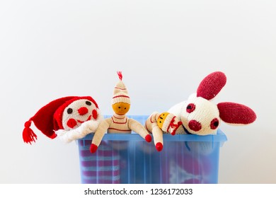 Cute and funny vintage children toys in a blue plastic box in front of a white wall. Assortment consists of a clown, a bunny and puppets.
