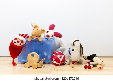 Cute and funny vintage children toys in a blue plastic box in front of a white wall. Assortment consists of a buffoon, a bunny, puppets, a squirrel, a wooden snail, a dog and a ball.