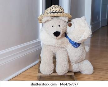 Cute giant mama teddy bear toy with bandana kneeling hugging giant papa rocking teddy bear wearing straw hat in home corridor
