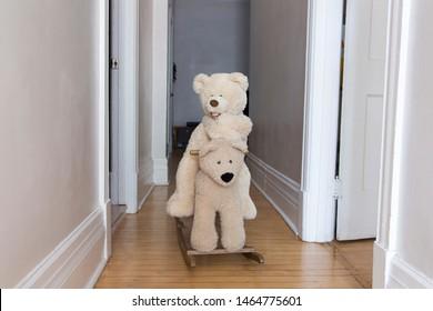 Cute giant mama teddy bear toy riding giant papa rocking teddy bear in home corridor
