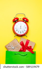 cute gifts in beautiful green shopping bag  and alarm clock on wonderful yellow background