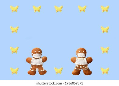 Cute gingerbread couple with protective face masks in a frame from butterflies, isolated, blue background. Greeting card, copy space for text. Creative concept in coronavirus (COVID-19) time