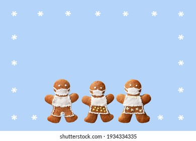 Cute gingerbread family with protective face masks in a frame from snowflakes, isolated, blue background. Greeting card, copy space for text. Creative concept in coronavirus (COVID-19) time