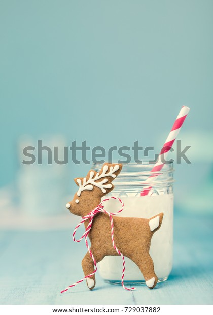 Cute gingerbread reindeer Christmas cookie with milk and straw over a blue background. Vintage syle.