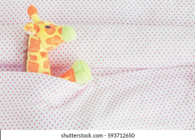 Cute giraffe lying down on the bed with pink blanket