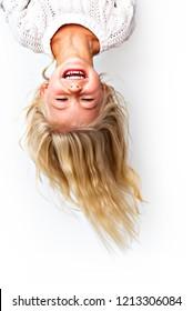 Cute girl 4-5 year old posing in studio upside down