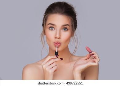 Cute girl applying lip gloss