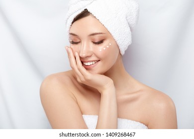 cute girl in bath towel and cream on the cheek looking down with smile, young happy woman moisturizing her face