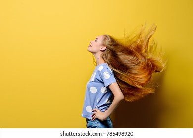 Cute girl with beautiful long flying hair over yellow background. Healthy hair, haircare.