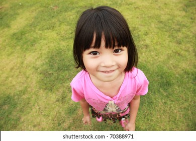 Cute girl with big eyes playing with camera.