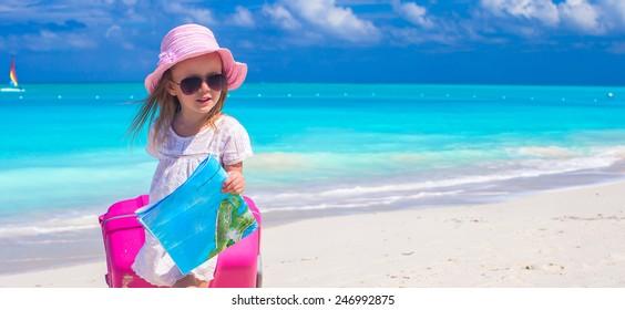 Cute girl with big luggage on white beach