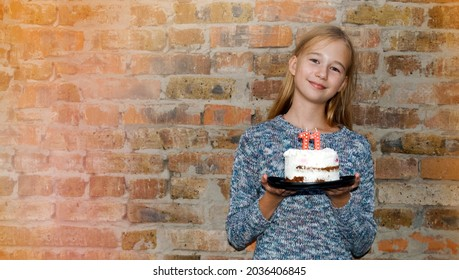 Cute girl with birthday cake, candles with number 11. The girl is celebrating her birthday.