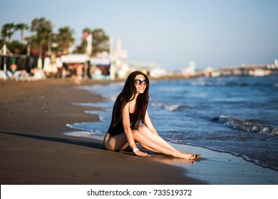 Cute girl in a black body posing by the sea