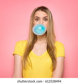 Cute girl blowing blue bubble gum near pink wall
