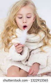 Cute girl blowing on a feather. Child.