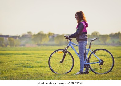 Cute girl with a blue bicycle in the countryside in spring. Front view. Copy space.