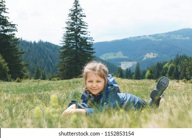 cute girl in blue coat laying in grass on meadow