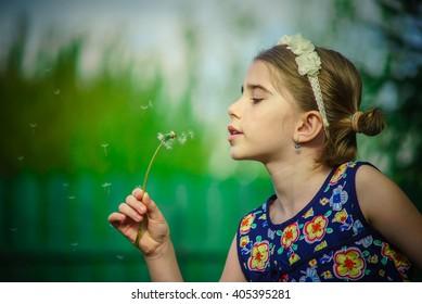 Cute girl in blue dress admiring a blown dandelion