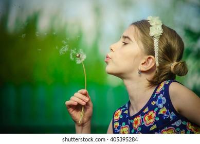 Cute girl in blue dress blowing a dandelion