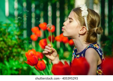 Cute girl in blue dress blowing a dandelion in a tulip garden