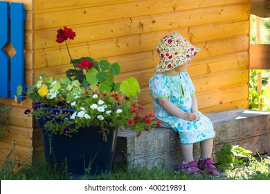 cute girl in blue dress and fruit design hat sitting in front children playhouse in the summer blooming countryside garden