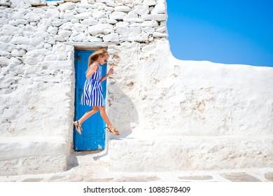 Cute girl in blue dress having fun outdoors near Paraportiani church in Mykonos