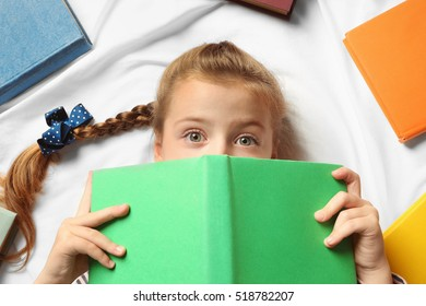 Cute girl with book lying on bed, closeup