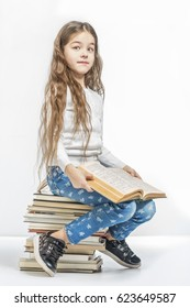 Cute girl with a book sitting on a pile of books on a white background