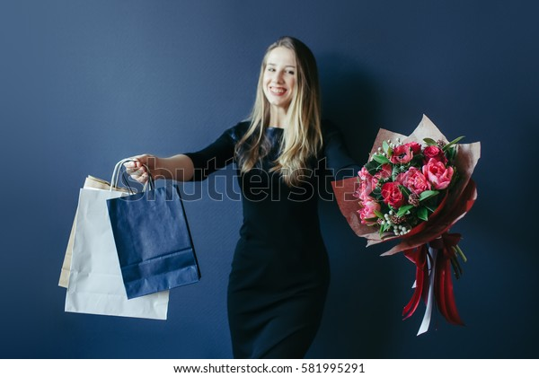 Cute girl with bouquet of red tulips and packages.