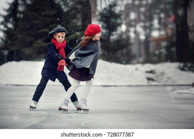 Cute girl and boy are having fun on the skating ring. Image with selective focus and toning.