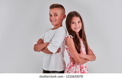 Cute girl and boy on a gray background are back to each other, arms crossed and smiling.