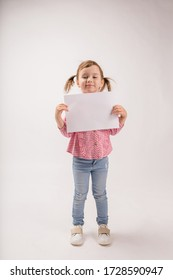 A cute girl with braids on a white background holds a white sheet with copy space. A little girl in a plaid shirt and jeans holds a leaf with an ad.