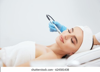 Cute girl with brown hair fixed behind,clean fresh skin naked shoulders wearing white bath robe and hair bandage, doing cosmetic procedure at light medical background, microdermabrasion.