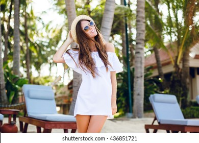 Cute girl in brown sunglasses and straw hat smiles widely and holds her hat with a hand. She wears white short dress with open shoulders. There are tropical trees behind her.
